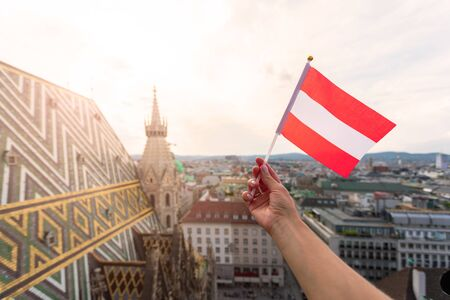 Woman holds Austria flag in hand against Vienna city panorama