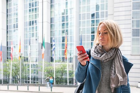 A young woman stands with a telephone in her hands opposite the European Parliament building in Brussels, Belgium. Stockfoto