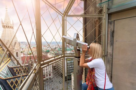 A young woman looks through observation binoculars and enjoys the panorama of the city in Vienna, Austria