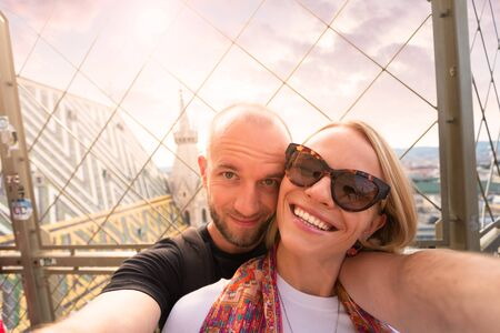 Young couple taking a selfie against the backdrop of the city panorama at sunset from the North Tower of St. Stephens Cathedral in Vienna, Austria