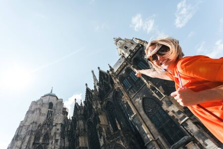 A young woman in a bright orange dress stands on the background of St. Stephens Cathedral in Vienna, Austria Reklamní fotografie - 129887267