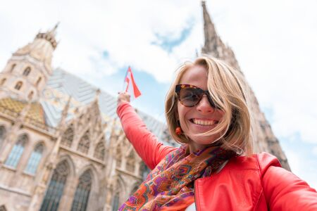 Woman stands on the background of St. Stephens Cathedral in Vienna with the flag of Austria in hand, Austria