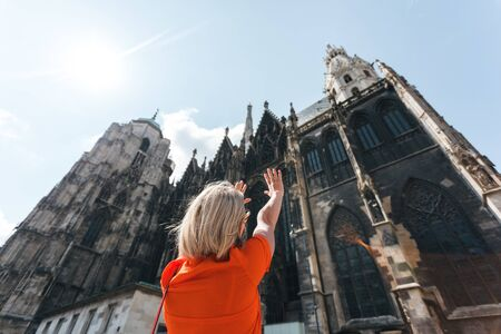 A young woman in a bright orange dress stands on the background of St. Stephens Cathedral in Vienna, Austria