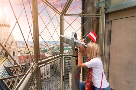 A young woman with the flag of Austria in her hands looks through observation binoculars and enjoys the panorama of the city in Vienna, Austria
