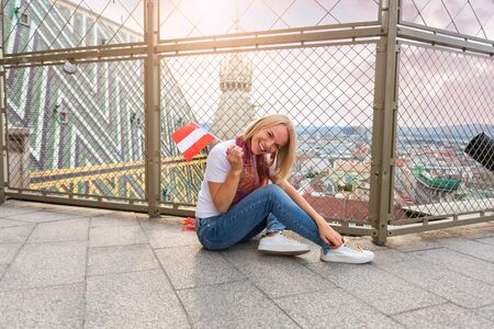 A young girl sits on the floor against the background of the panorama of Vienna and against the roof of St. Stephens Cathedral in Vienna.