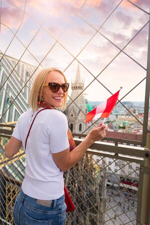 A woman admires the panorama of Vienna from the viewpoint of St. Stephens Cathedral and holds the flag of Austria in her hands. Reklamní fotografie - 129887146