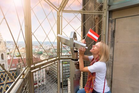 A young woman with the flag of Austria in her hands looks through observation binoculars and enjoys the panorama of the city in Vienna, Austria Reklamní fotografie - 129887144