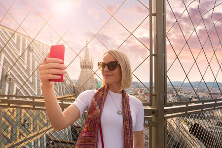 A woman takes a selfie picture on her phone on the roof of St. Stephens Cathedral in Vienna, Austria
