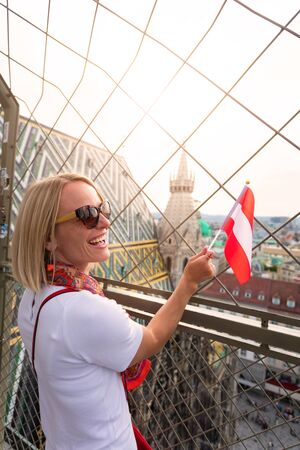A woman admires the panorama of Vienna from the viewpoint of St. Stephens Cathedral and holds the flag of Austria in her hands. Reklamní fotografie - 129884799