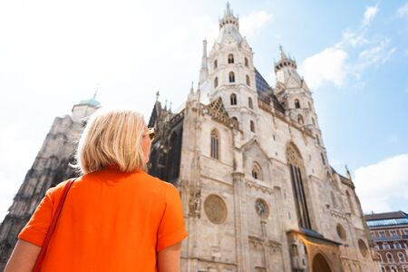 A young woman in a bright orange dress stands on the background of St. Stephens Cathedral in Vienna, Austria 免版税图像