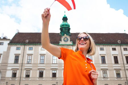 Young woman tourist stands with a Austria flag