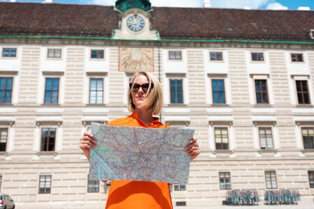 Young woman tourist stands with a city map Foto de archivo - 133745261
