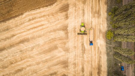 A beautiful new combine harvester dumps grain into a truck trailer on the field. Aerial view