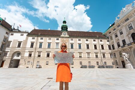 Young woman tourist stands with a city map on the background of the Hofburg courtyard in Vienna, Austria Foto de archivo - 133745270