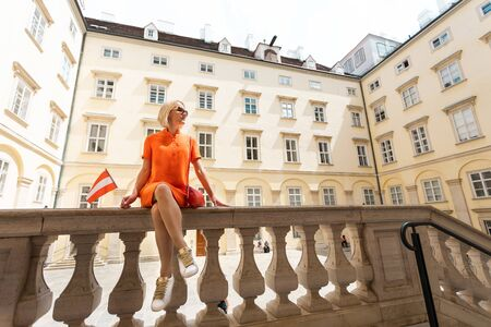 A woman in an orange dress stands in one of the courtyards of the Hofburg with the red-and-white flag of Austria in Vienna, Austria Foto de archivo - 133745276