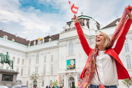 Woman tourist stands against the backdrop of the Austrian National Library in Vienna with raised arms and the flag of Austria, Vienna