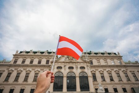 Flag of Austria against the backdrop of the Schonbrunn Palace in Vienna, Austria