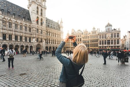 Woman stands in the square Grand Place in Brussels, Belgium at sunset. Photos for Social Networks