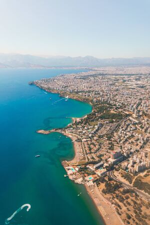 The view from the airplane window on the coast of Antalya with many houses, hotels, etc. with beautiful Taurus Mountains on the horizon, Turkey. A speed boat is sailing in the Mediterranean Sea. Aerial view Reklamní fotografie