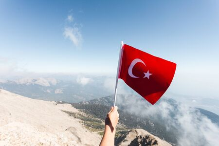 Turkey flag in a female hand against the backdrop of Taurus Mountains from a viewpoint of Tahtali Mountain. Tahtali Dagi, Antalya Province, Turkey