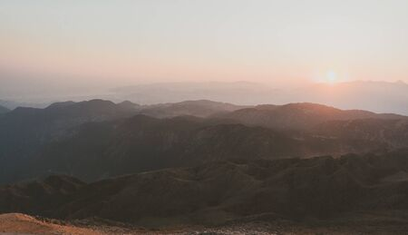 Beautiful mountain landscape with sunset over Taurus Mountains from the top of Tahtali Mountain near Kemer, Antalya, Turkey. Photo in orange and blue natural tones.