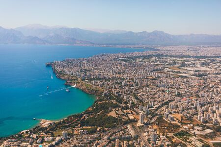 The view from the airplane window on the coast of Antalya with many houses, hotels, etc. with beautiful Taurus Mountains on the horizon, Turkey