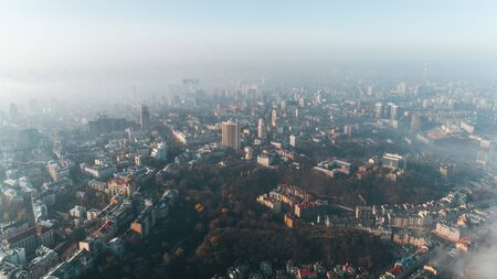 Aerial view of the morning city covered with thick fog at sunrise. Apocalyptic picture of the city in the haze.