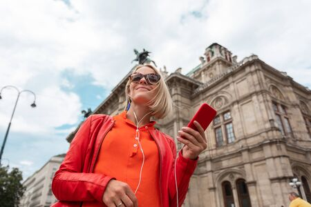 Young girl listens to music with headphones in front of Vienna State Opera, Austria