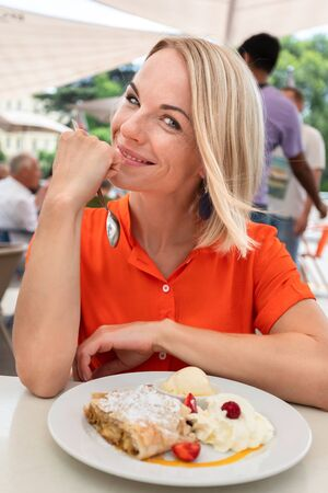 Young beautiful smiling woman is sitting on the street in a cafe or restaurant with dessert and looking at the camera