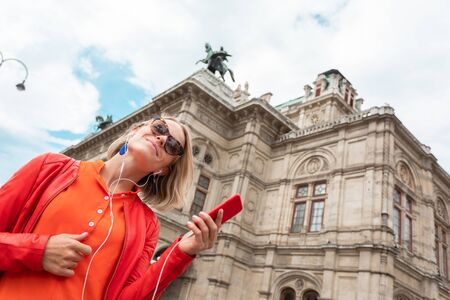 Young beautiful smiling woman listens to music with headphones in front of Vienna State Opera, Austria Reklamní fotografie