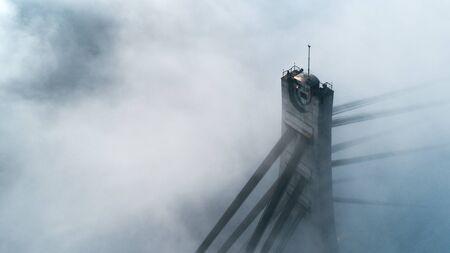 The top of the pylon of the North Bridge or Moscow Bridge in dense dense fog in Kiev, Ukraine. City in the mist