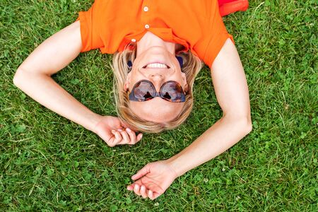 Top view of a beautiful young woman in a bright orange dress lying on the grass and smiling sweetly. Reklamní fotografie