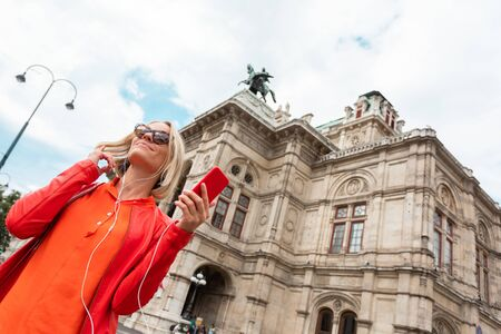 Young beautiful smiling woman listens to music with headphones in front of Vienna State Opera, Austria