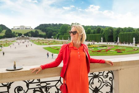 Young female tourist stands against a Schoenbrunn palace park in Vienna, Austria Imagens