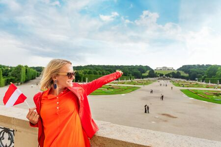 Young female tourist with the flag of Austria stands against a Schoenbrunn palace park in Vienna, Austria