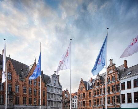 View of traditional Flemish houses in the Grote Markt square or Market Square in Bruges with flags on which Brugge is written in the foreground, Belgium Imagens