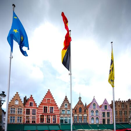View of the colorful houses on Grote Markt or Market Square in Bruges with the flags of Belgium, the European Union and the city of Bruges in the foreground, Belgium Imagens