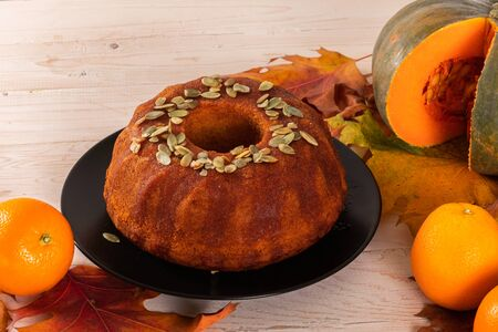 Bright autumn Pound pumpkin cake watered with orange syrup and garnished with pumpkin seeds on the background of autumn bright orange leaves. Imagens