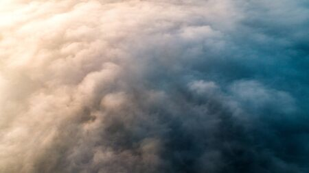 Background from the thick morning blue fog consisting of large and intense white clouds with warm backlight from the rising sun. Texture for work, place for text. Imagens