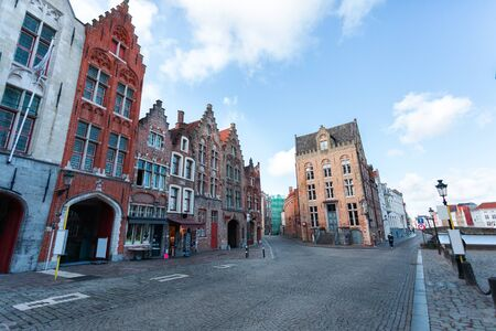 Typical street in the historical part of Bruges with small colored houses in the Flemish style, cozy cafes, restaurants and shops, Belgium