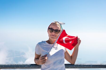 Young woman tourist in denim shorts and a white T-shirt stands on a viewing platform of Tahtali Mountain in Kemer with a red Turkey flag in hands Banco de Imagens