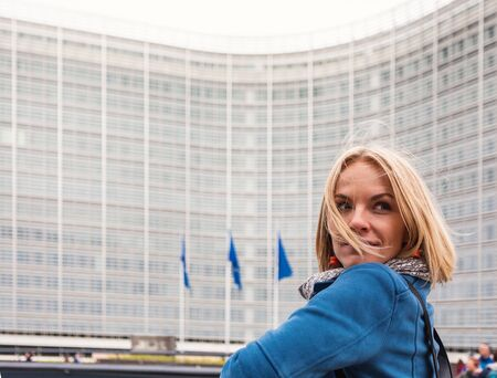 A young woman stands against the backdrop of the European Commission headquarters in Brussels, Belgium