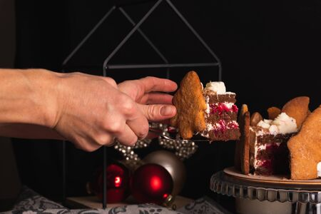 Female hands carry a piece of cake Black Forest decorated in a Christmas style with ginger cookies on a plate on a dark background Stockfoto