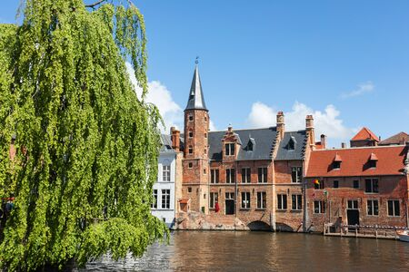 Beautiful landscape on classic houses in the Flemish style with reflection in the water of canals in the historical center of Bruges, Belgium
