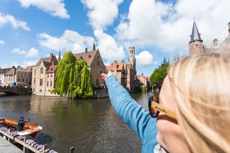 Girl shows a hand in the direction of the famous tourist destination in Bruges, Belgium Foto de archivo - 136320773