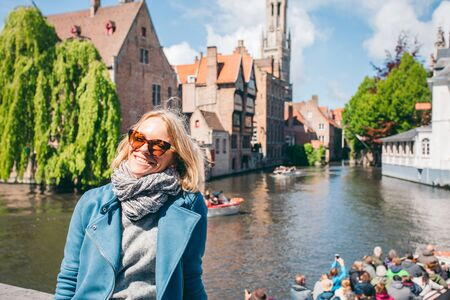 A beautiful young girl sits of a famous tourist spot with a canal in Bruges, Belgium Foto de archivo - 136321083