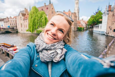 Beautiful young girl takes selfie photo of the famous tourist destination with a canal in Bruges, Belgium Foto de archivo - 136321084