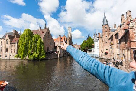 A young girl shows her hand in the direction of a famous tourist destination in Bruges, Belgium Foto de archivo - 136321085