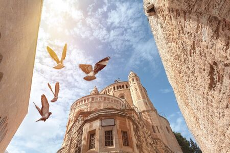View of the top of the Franciscan Monastery in Jerusalem or Dormishen Abbey with flying doves, Israel