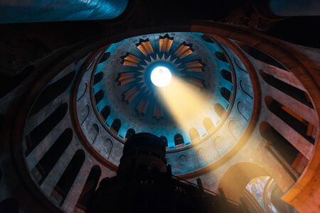 Interior of the Temple of the Holy Sepulcher in Jerusalem with a ray of sunshine through an opening in the dome, Israel